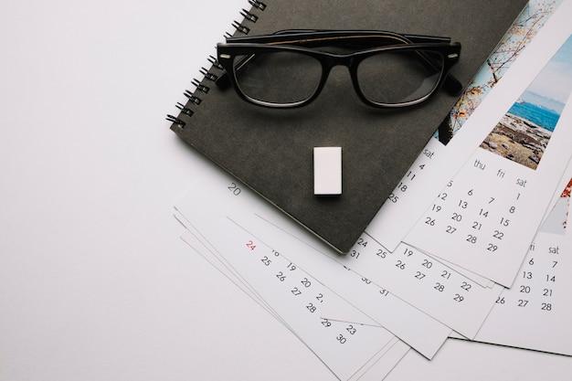 Óculos no caderno e calendários