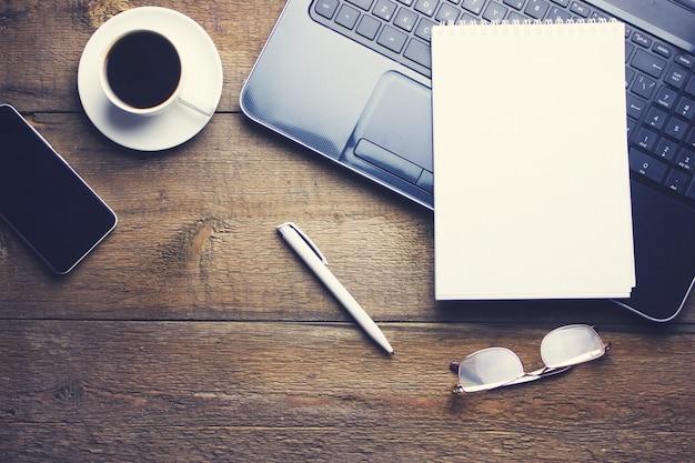 Óculos no computador, xícara de café e papel na mesa de madeira