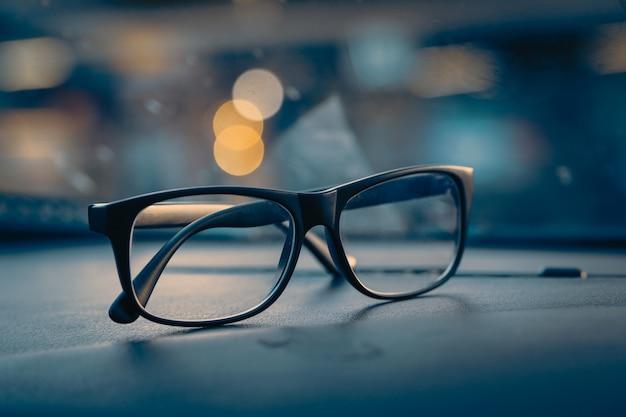 Óculos no console do carro com luz da cidade