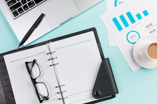 Óculos no diário, laptop, caneta, xícara de café e plano de orçamento na mesa de escritório