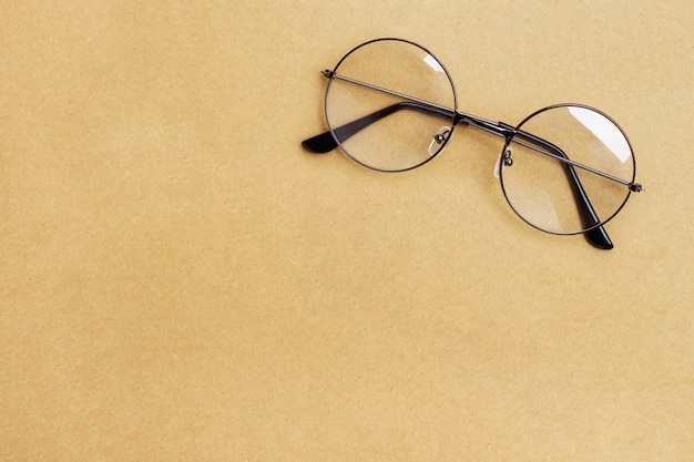 Óculos no fundo de papel pardo.