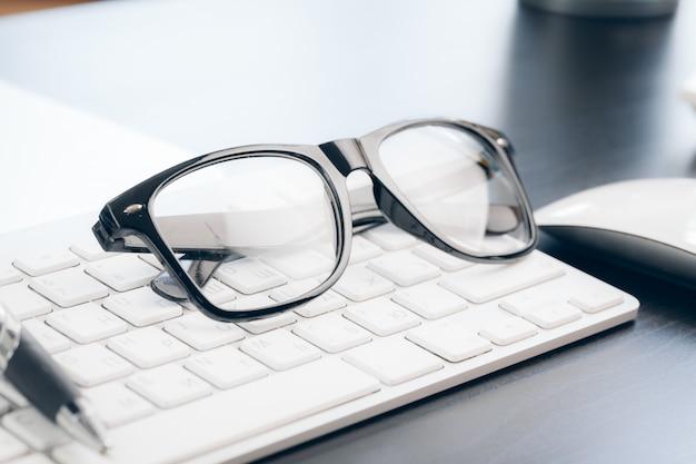 Óculos no laptop com caneta, close-up