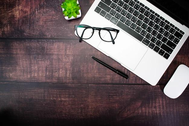 Óculos no laptop de um empresário com acessórios em uma mesa de madeira velha moderna com cópia.