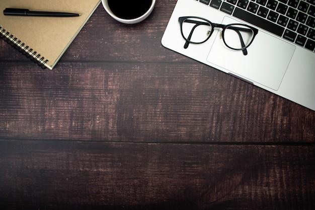 Óculos no laptop do empresário com acessórios na mesa de madeira velha, na vista superior e com cópia.