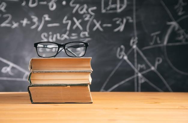 Óculos no livro no quadro-negro