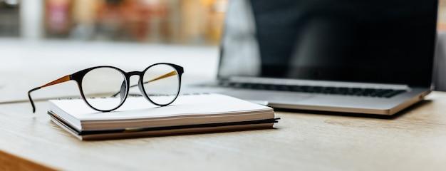 Óculos no local de trabalho no escritório perto do laptop e do bloco de notas. horário comercial