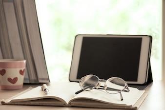 Óculos no notebook com tablet digital no local de trabalho no dia chuvoso