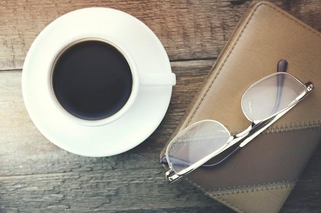 Óculos no notebook com uma xícara de café na mesa de madeira