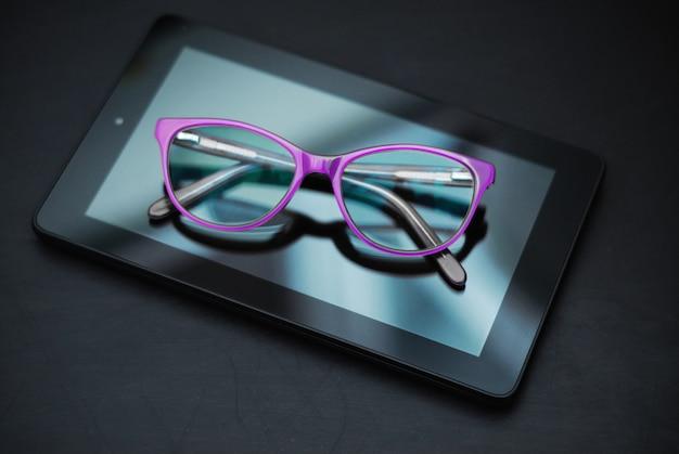 Óculos no tablet mais escuro. educação, technoogy, internet.