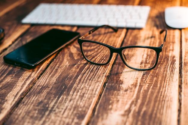 Óculos para correção da visão e da visão e proteção do computador na mesa de madeira