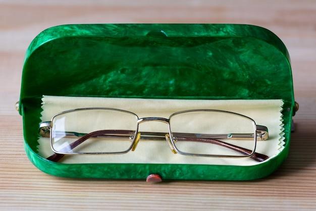 Óculos para olhos em caixa verde e pano de limpeza.