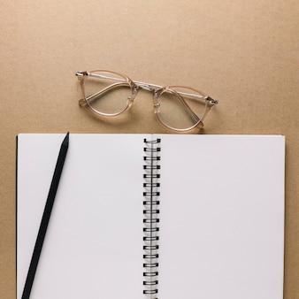 Óculos perto de caderno e lápis