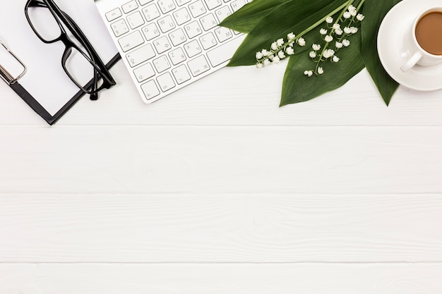 Óculos, prancheta, teclado, flor e folhas com xícara de café na mesa de escritório