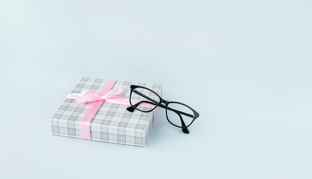Óculos pretos e caixa de presente em fundo azul claro