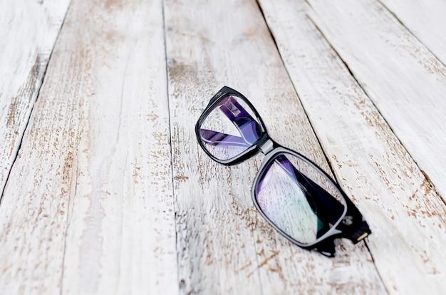 Óculos pretos em fundo de madeira