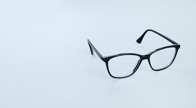 Óculos pretos em imagem de fundo azul claro com espaço de cópia