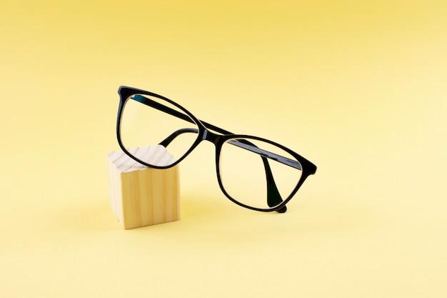 Óculos pretos na superfície amarela
