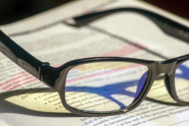Óculos pretos no livro de economia sobre fundo desfocado na biblioteca