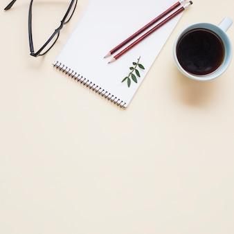 Óculos pretos; xícara de chá e dois lápis no bloco de notas em espiral contra o pano de fundo bege