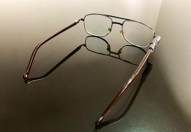 Óculos quebrados na mesa de vidro, foco superficial