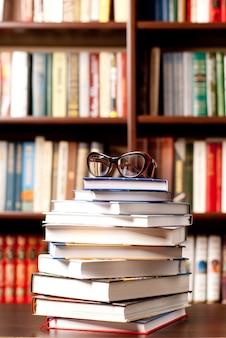 Óculos sobre o livro aberto e muitos outros livros no fundo