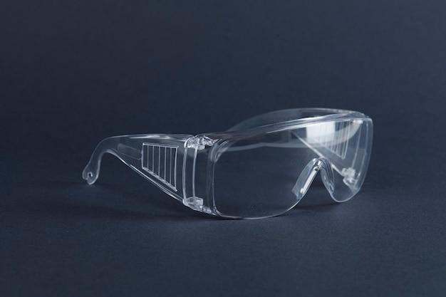 Óculos transparentes em uma superfície azul escura