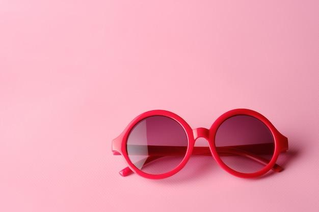 Óculos vermelhos em fundo rosa com espaço de cópia