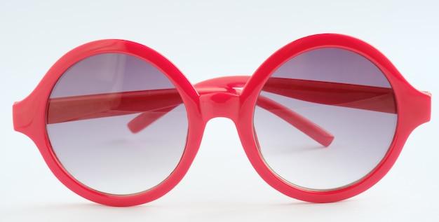 Óculos vermelhos sobre fundo branco, close-up objeto