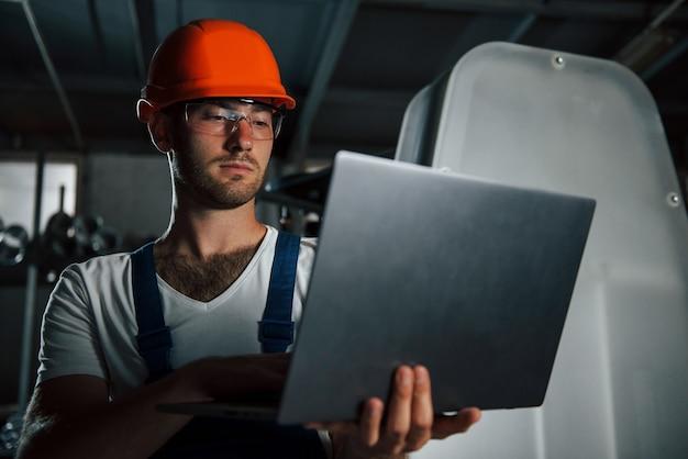 Ocupação de engenheiro. homem de uniforme trabalha na produção. tecnologia industrial moderna.