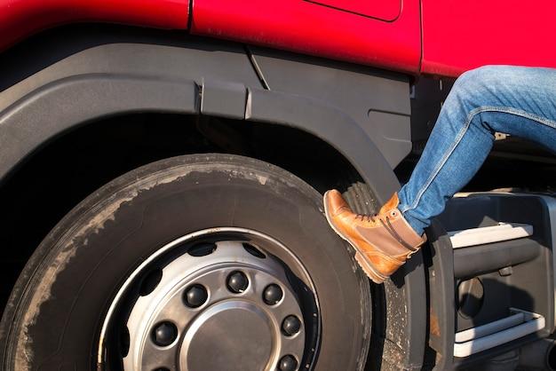 Ocupação do caminhoneiro e botas do motorista no volante.