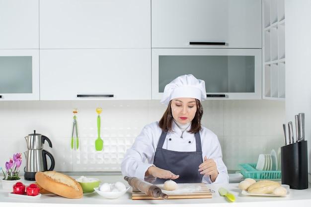 Ocupada chef de uniforme, em pé atrás da mesa, manchando o rosto com farinha na cozinha branca