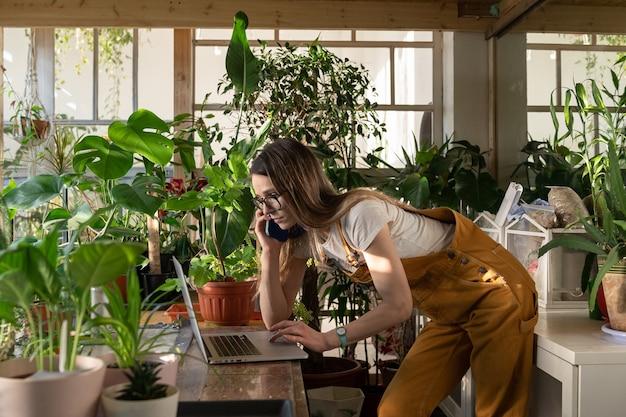 Ocupada empresária freelancer ou jardineira trabalhando em um laptop em casa com plantas Foto Premium