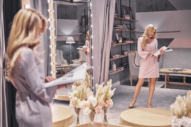 Ocupado com a escolha. reflexo de corpo inteiro de uma jovem atraente em um vestido elegante lendo uma revista enquanto estava na loja de noivas