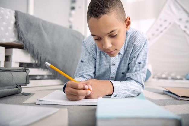 Ocupado com o dever de casa. rapaz inteligente afro-americano a posar no chão enquanto escreve no caderno