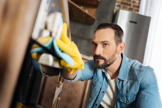 Ocupado e atraente limpador masculino trabalhando e limpando impressões digitais enquanto calça luvas