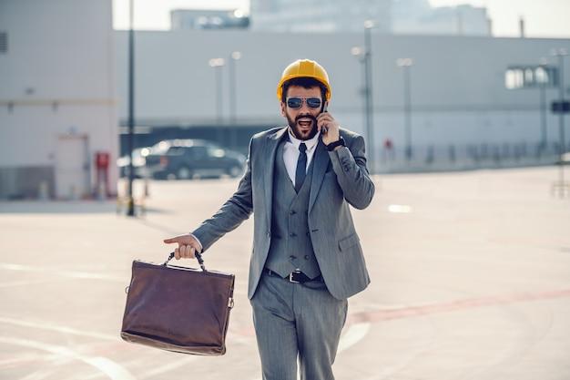 Ocupado empresário barbudo caucasiano atraente de terno, com óculos escuros e capacete na cabeça, segurando a mala e falando ao telefone enquanto vai no canteiro de obras.