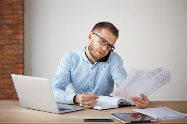Ocupado empresário concentrado de óculos e camisa, sentado em um escritório confortável