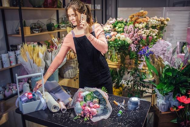 Ocupado jovem florista feminina falar no telefone. ela alcança a cesta de madeira com fitas coloridas. jovem de pé na sala cheia de flores e plantas.