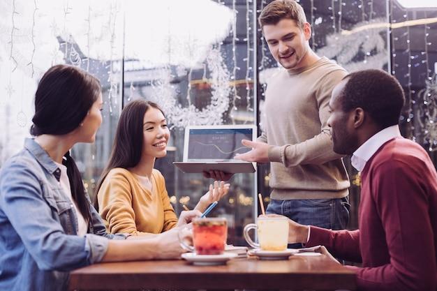 Ocupados, agradáveis quatro colegas trabalhando na estratégia enquanto trazem ideias e sorriem