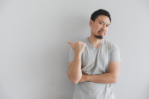 Odeie a cara do homem no t-shirt cinzento com ponto da mão no espaço vazio.