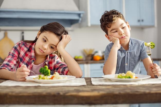 Odiamos vegetais. atraente irmão e irmã mais novo, de cabelos escuros, sentados à mesa tomando um café da manhã saudável e olhando tristemente para os vegetais