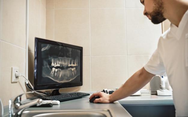 Odontologia com dentista cardíaco olhando para a imagem do raio x de maxilares no monitor digital do computador