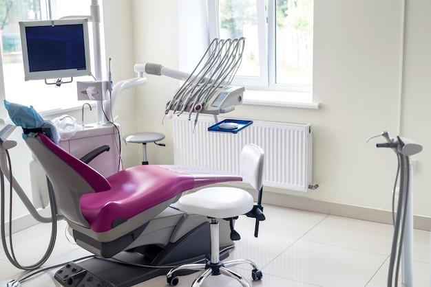 Odontologia dentro, cadeira violeta para paciente e equipamentos