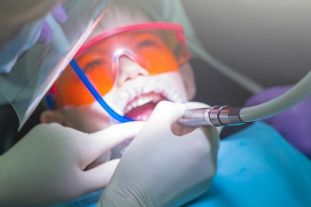 Odontologia para crianças. dentes de bebê de exame de dentista infantil. garotinho em óculos de proteção laranja e cofferdam. cárie de tratamento de processo.