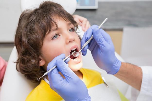 Odontologia pediátrica examinando dentes de meninos na cadeira de dentistas