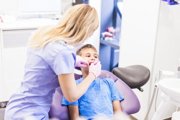 Odontólogo, fazendo, tratamento dental, de, um, menino, em, clínica
