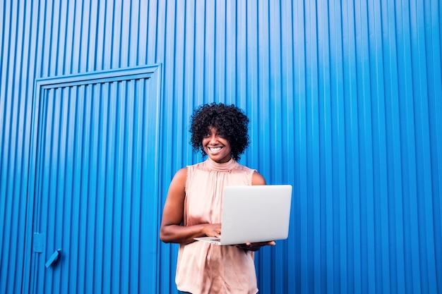 Oe linda mulher negra africana ou americana sorrindo e usando laptop ou computador pc curtindo a tecnologia - alegre jovem se divertindo usando o dispositivo de tecnologia
