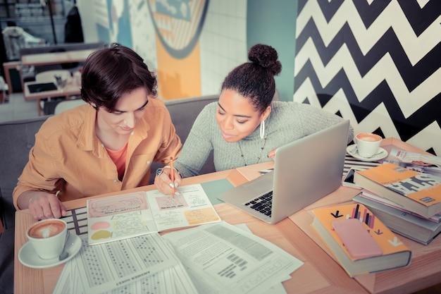 Oferecendo ajuda ao colega de grupo. a aluna ajudando sua colega de grupo com a difícil tarefa de casa