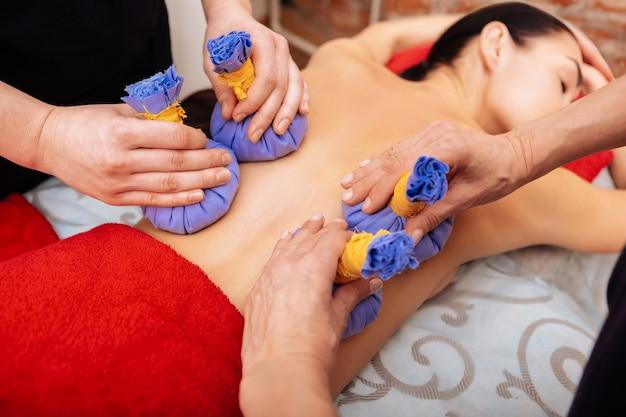 Oferecendo massagem. trabalhadores experientes carregando sacolas de ervas azuis nas costas de um cliente adormecido
