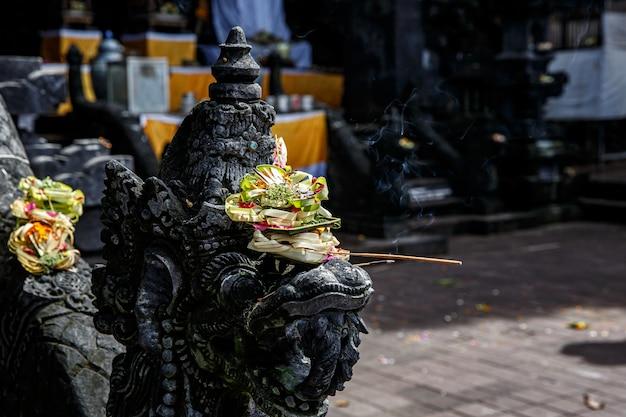 Ofertas tradicionais balinesas aos deuses em bali com flores e palitos aromáticos.